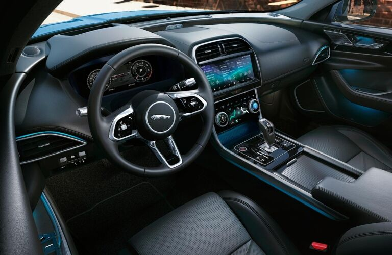 Interior view of the black front seating, steering wheel and touchscreens inside a 2020 Jaguar XE