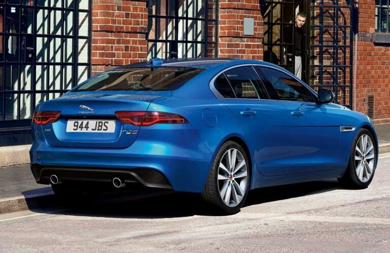 Exterior view of the rear of a blue 2020 Jaguar XE parked on a city street