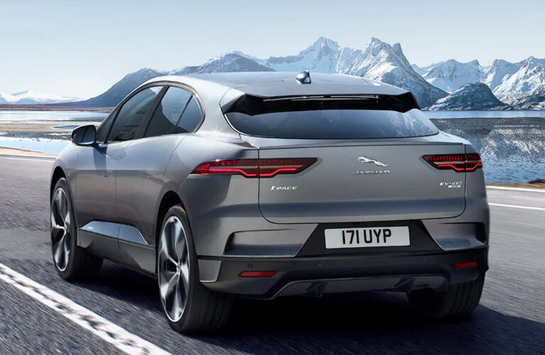 Rear view of grey 2020 Jaguar I-PACE with snowy mountains in the background