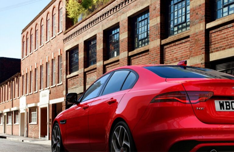 Red 2020 Jaguar XE driving by a brick building