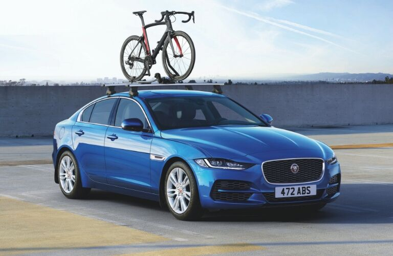 A bicycle attached to a roof rack on a blue 2020 Jaguar XE