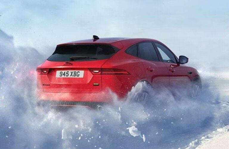 Red 2021 Jaguar E-PACE driving through snow