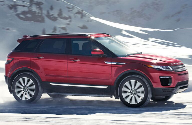 side profile of red Land Rover Range Rover Evoque driving through snowy mountains