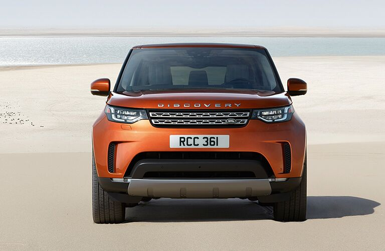 front view of orange land rover discovery parked on beach