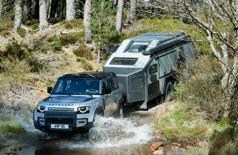 2020 Land Rover Defender towing trailer through water