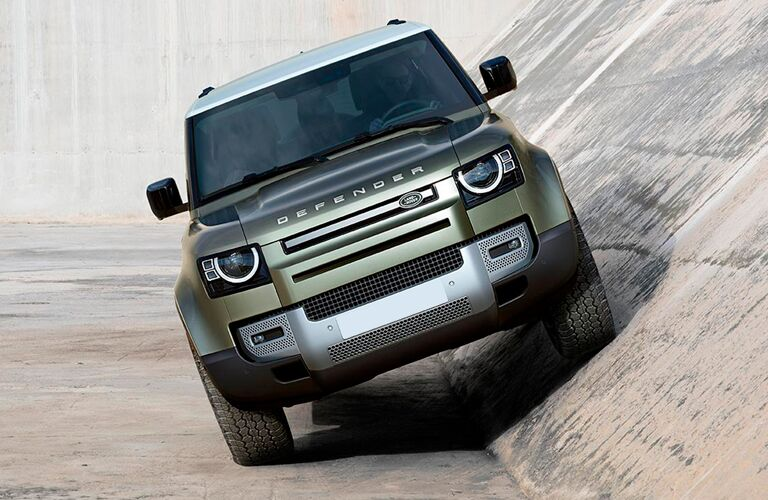 The front side of a light green 2021 Land Rover Defender driving at an angle.