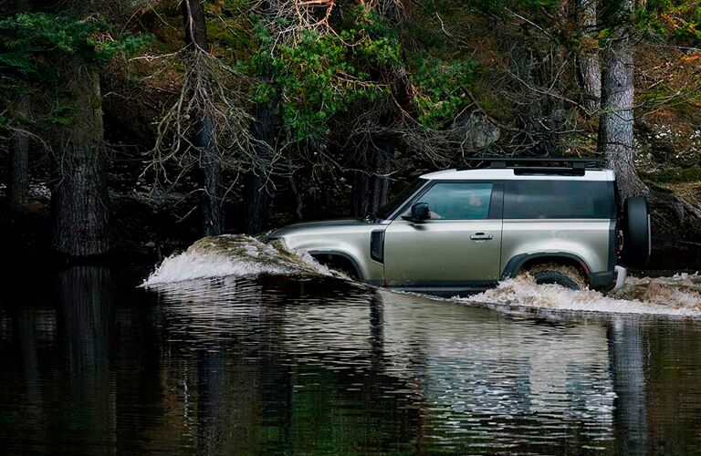 Te side view of a light green 2021 land Rover Defender fording a river.