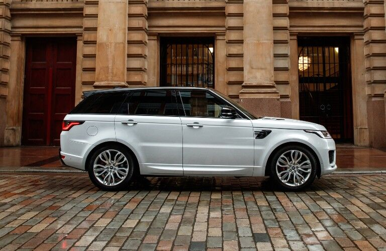 The side view of a light gray 2021 Land Rover Range Rover Sport parked on a street.