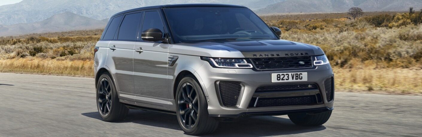 The front and side view of a silver 2021 Land Rover Range Rover Sport model driving down a road.