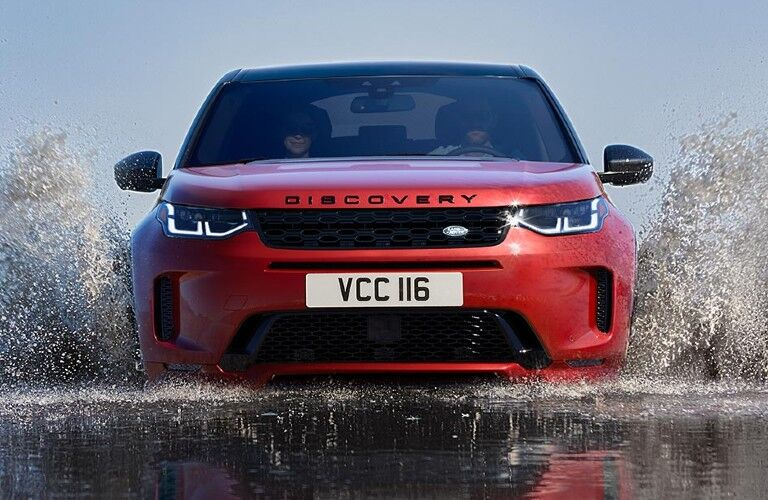Red 2020 Land Rover Discovery Sport driving through a stream