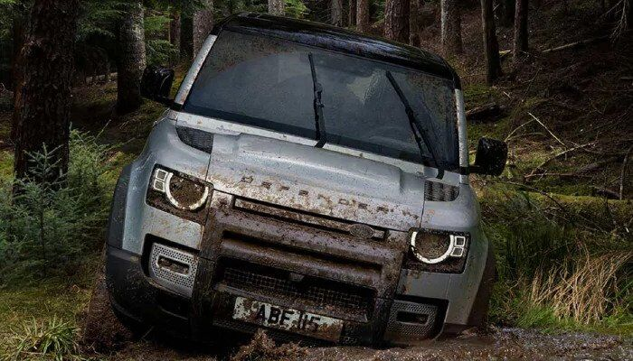 Land Rover Defender driving through muddy forest