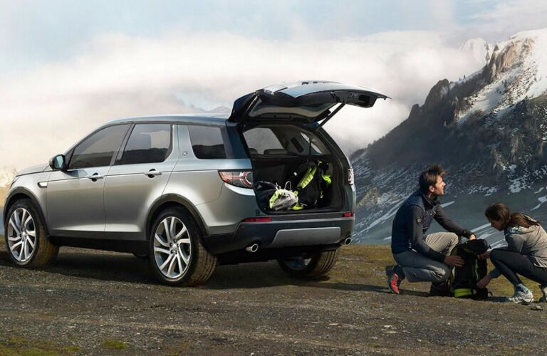 man and woman unpacking cargo from rear of 2018 Land Rover Discovery Sport with mountain in background