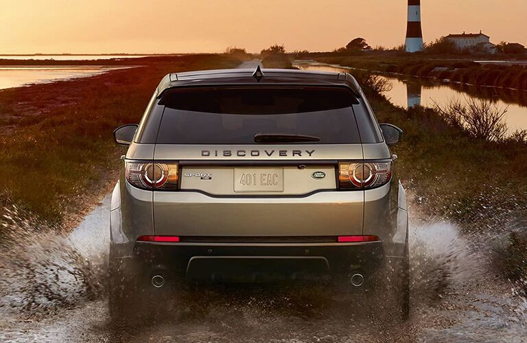 rear end of land rover discovery sport driving through mud