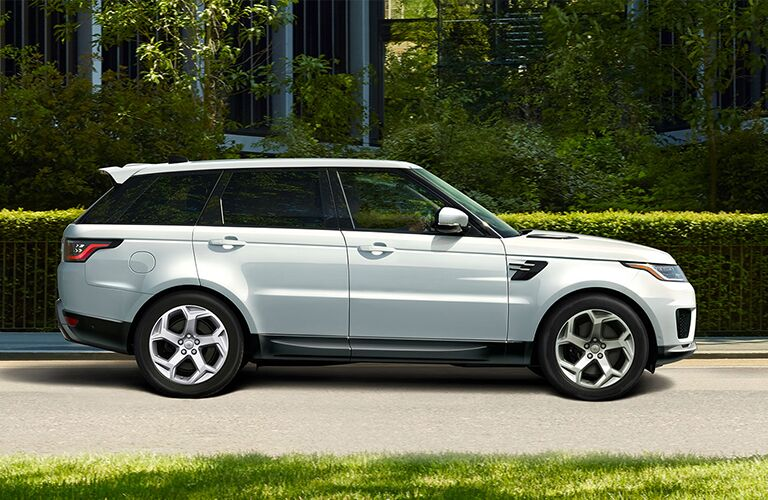 Profile view of silver Land Rover Range Rover Sport parked in front of hedges