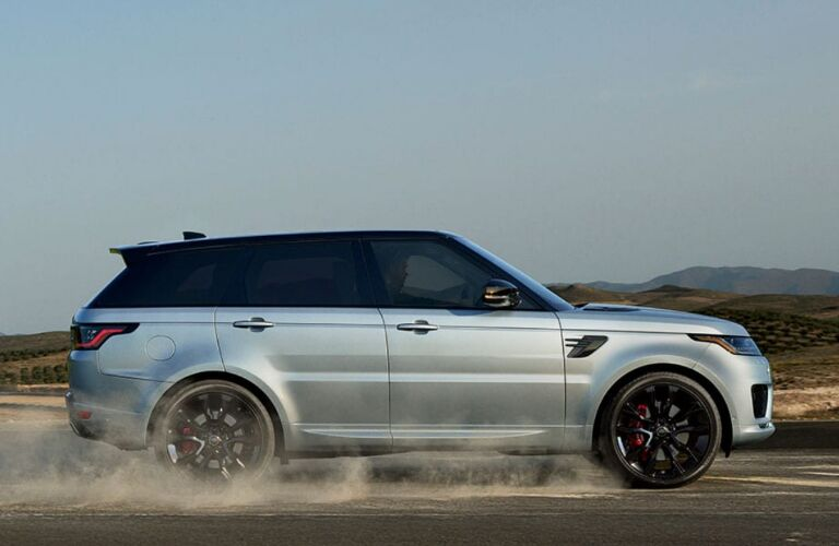 Silver 2020 Land Rover Range Rover Sport driving on a dusty road