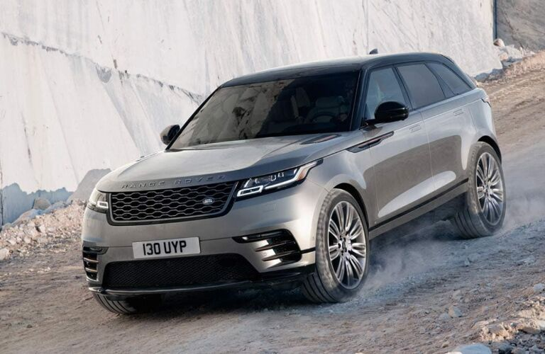 Silver and black 2020 Land Rover Range Rover Velar driving down a steep gravel road