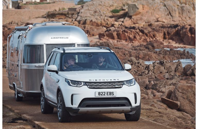 2020 Land Rover discovery exterior shot from front white paint pulling trailer thorugh desert road