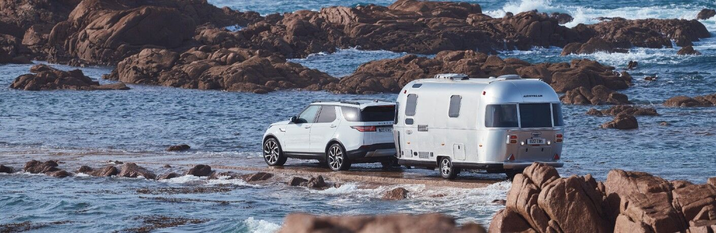 2020 Land Rover white paint exterior shot from behind  towing trailer on rocky shore