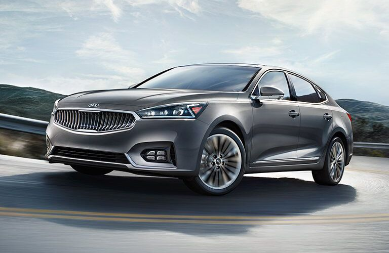 2018 Kia Cadenza taking a curve on a road