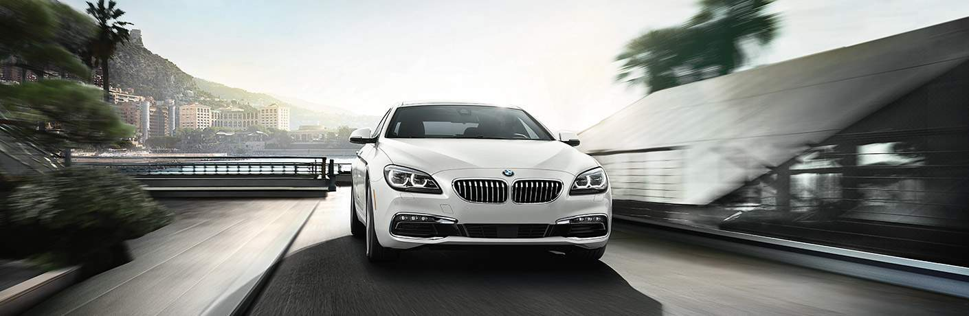 white bmw series 6 model parked in a city by waterfront and bushes.