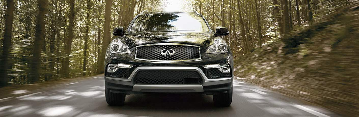 The front end of the 2017 Infiniti QX50 driving down a road surrounded by trees
