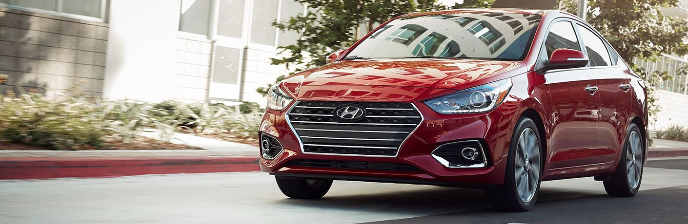 Red 2019 Hyundai Accent driving on residential street