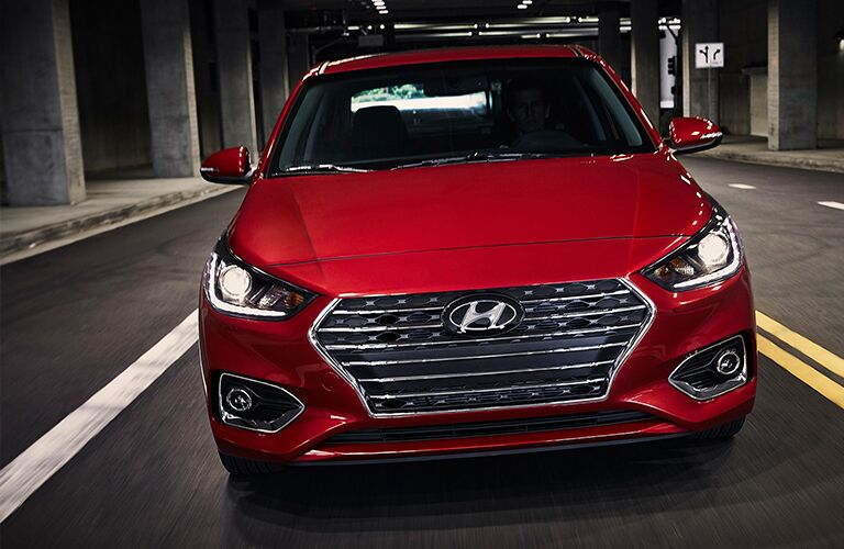 Front view of red 2019 Hyundai Accent driving through tunnel under bridge