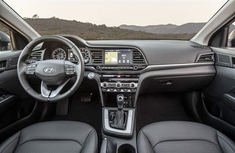 Interior of the 2019 Hyundai Elantra in the front showing the wheel, transmission, and touchscreen
