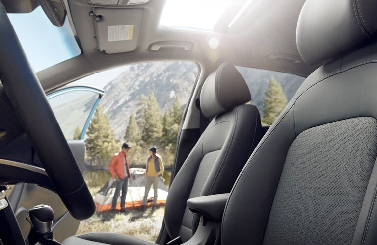 Seats in the 2019 Hyundai Kona with the Passenger Door Open and a Couple in the Background with Camping Gear