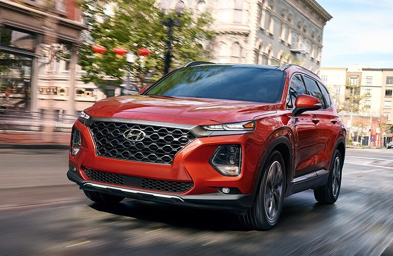 Front Driver View of a Red 2019 Hyundai Santa Fe Driving Down a Road