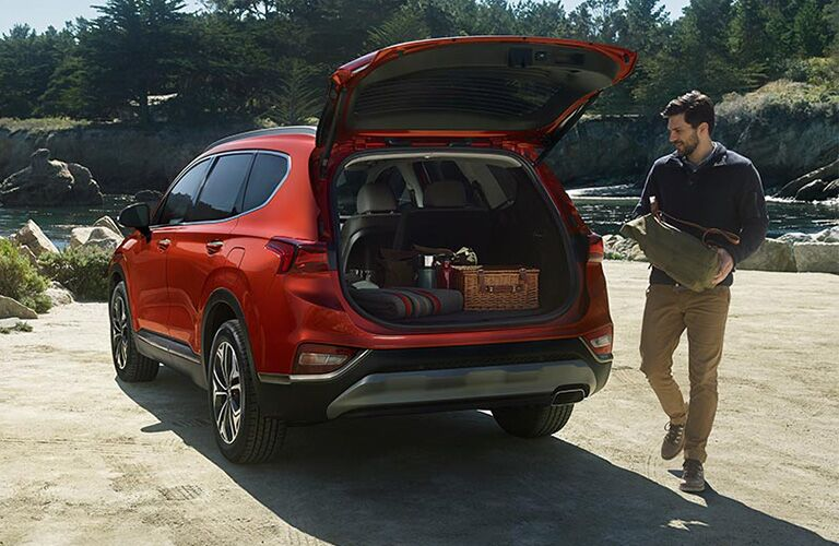 Rear Driver side of a Red 2019 Hyundai Santa Fe with the back open and a man loading belongings inside