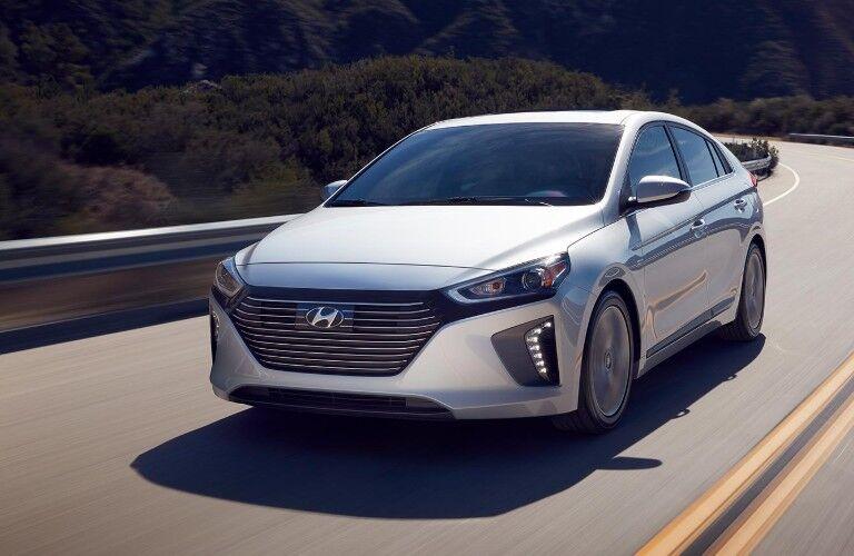 A white 2019 Hyundai Ioniq driving down a road