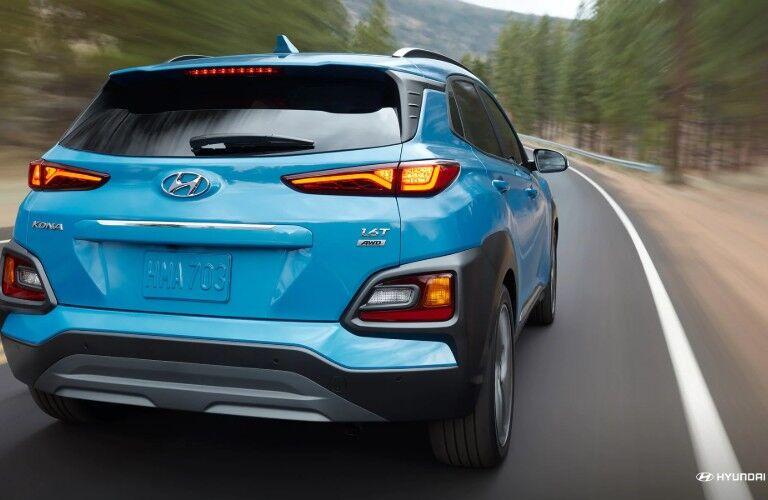 Rear shot of blue 2019 Hyundai Kona driving on tree-lined road