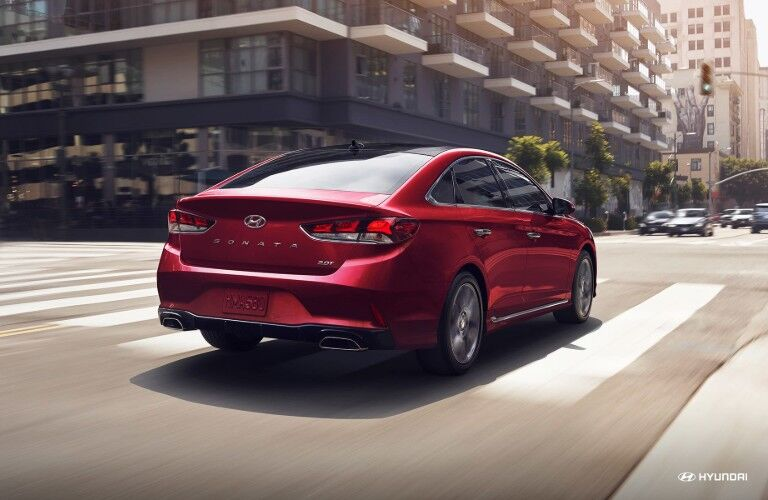 Rear shot of red 2019 Hyundai Sonata driving through city