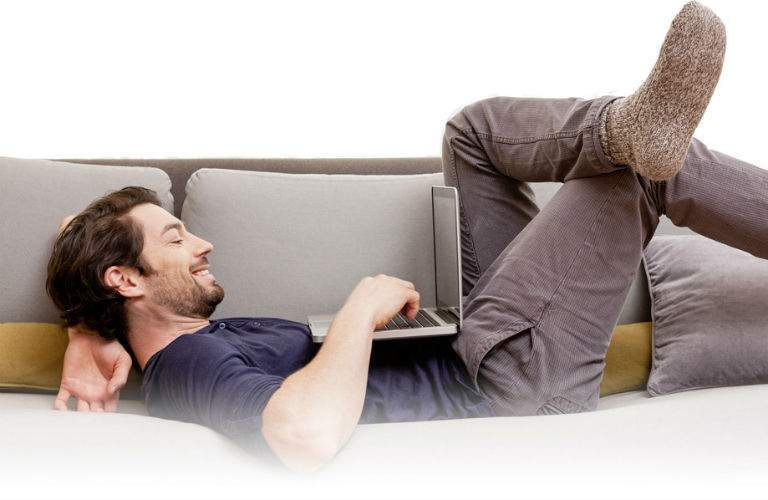 Male Shopper Shopping From Comfort of Home on Couch
