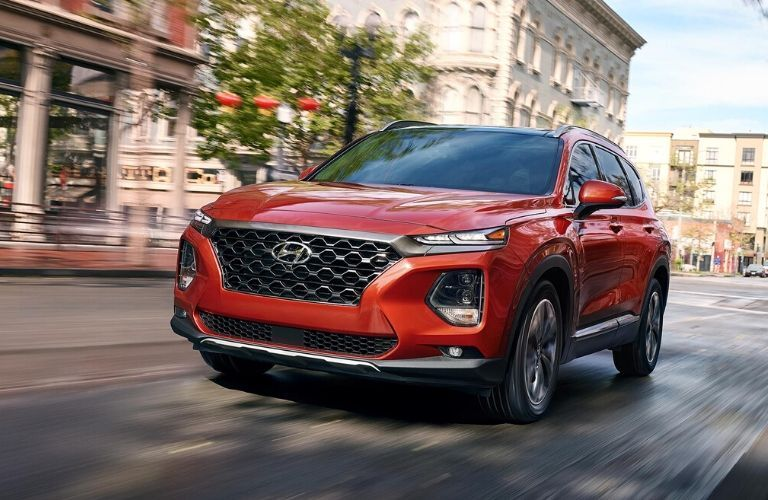 Red 2020 Hyundai Santa Fe driving down road from front driver side