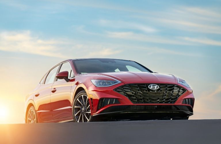 Red 2020 Hyundai Sonata from lower front angle with sunset