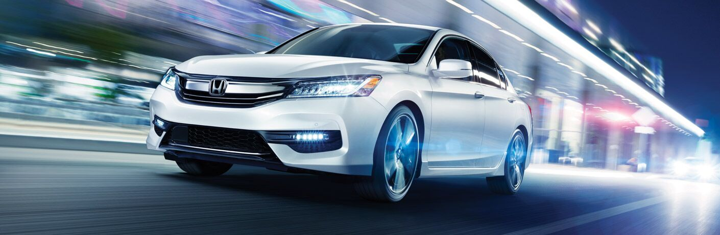 2017 Honda Accord driving through a city with a blur of lights in the background