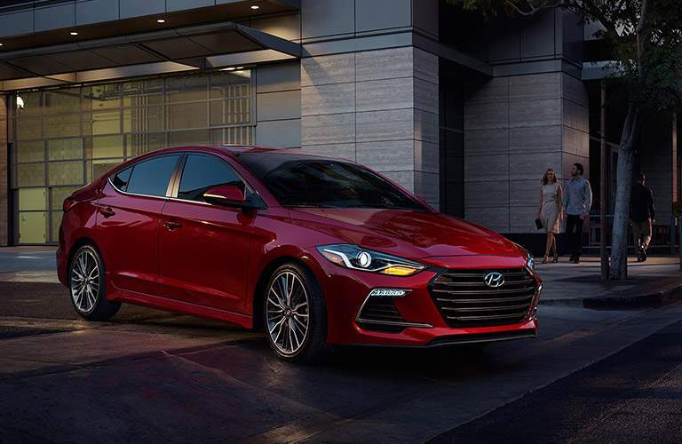 front view of a red 2018 Hyundai Elantra parked in front of a building