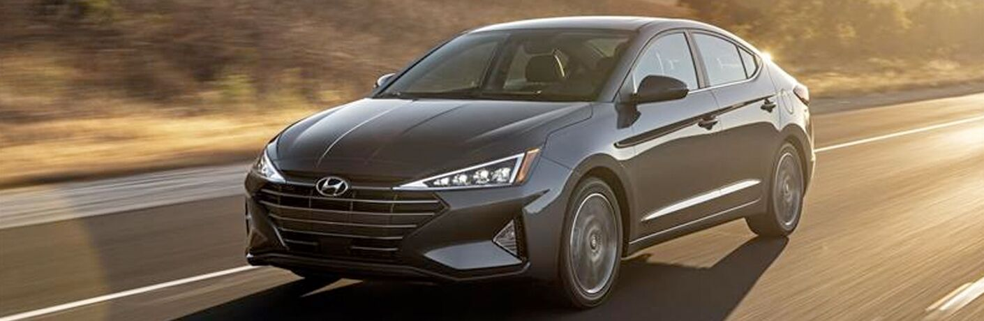 2019 Hyundai Elantra exterior shot with dark gray metallic paint color driving down a country highway as the sun sets behind it