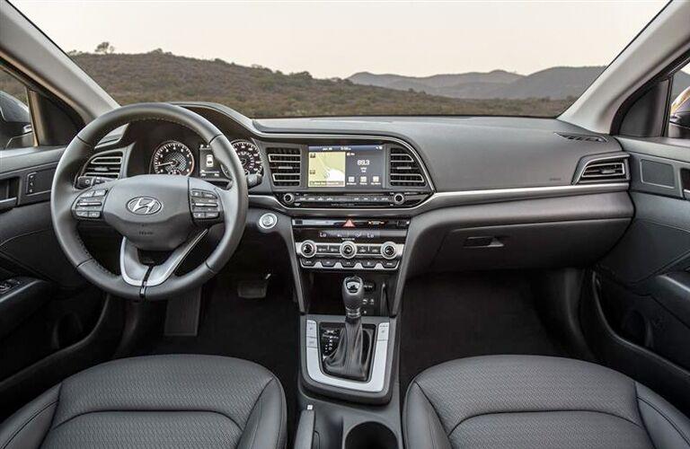 2019 Hyundai Elantra interior shot of front seating, steering wheel, and dashboard layout