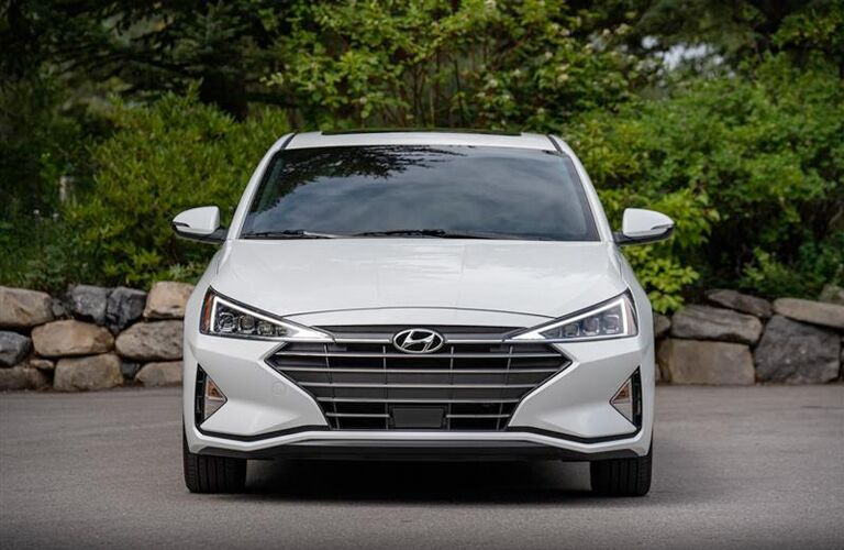 2019 Hyundai Elantra exterior front shot with white paint color parked in front of a short brick wall housing green bushes