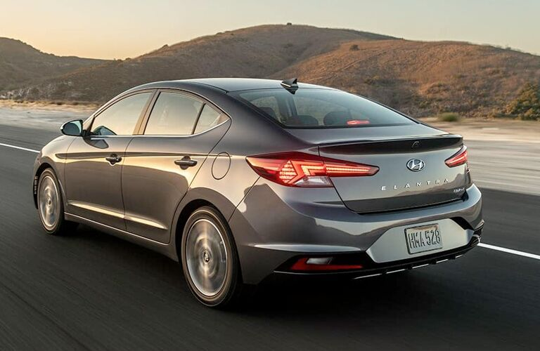 2019 Hyundai Elantra exterior rear shot with gray metallic paint color driving down a country desert road