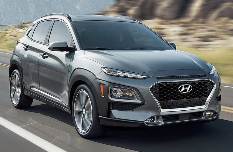 2019 Hyundai Kona exterior shot with gray paint color driving between grassy mountains cliffs