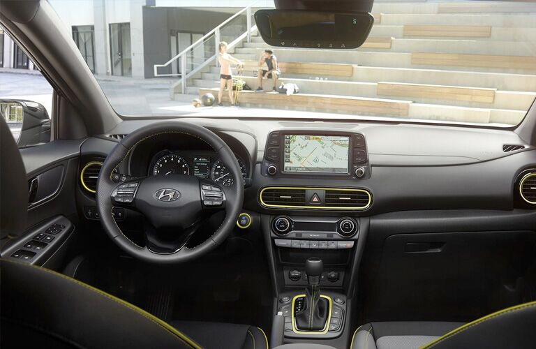 2019 Hyundai Kona interior shot of steering wheel and dashboard layout while a couple of children sit outside on stone steps