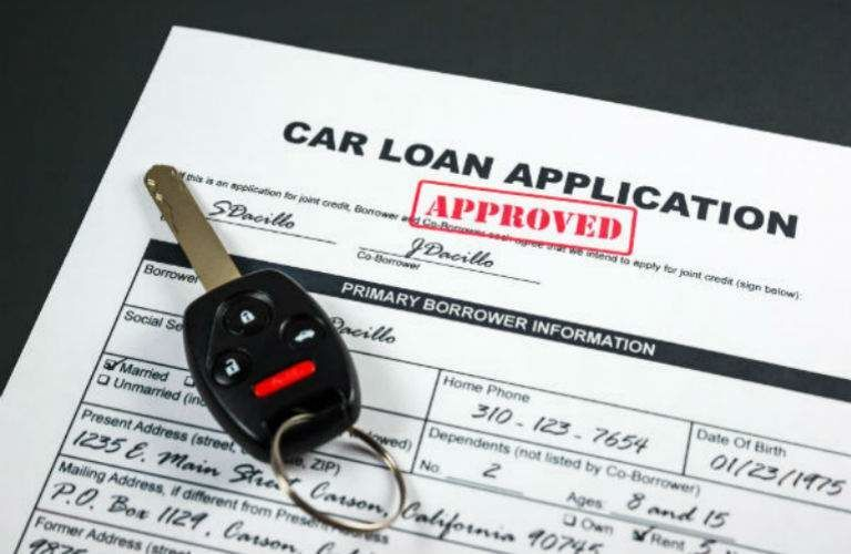 Set of keys and car loan papers with approved stamped on it