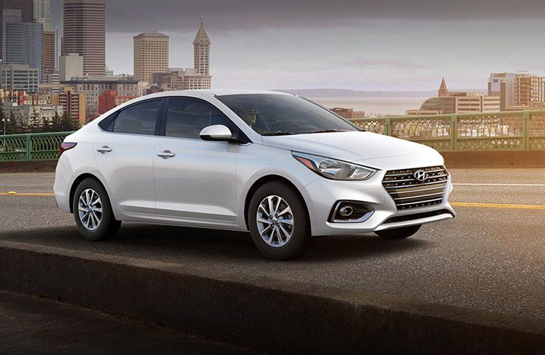 2019 Hyundai Accent exterior side shot with white paint color parked next to a bridge with a line of skyscrapers behind it