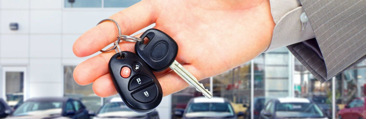 Hand holding keys to new car