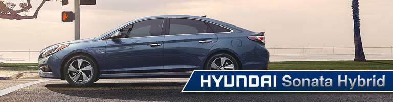 blue Hyundai Sonata Hybrid stopped at a red light