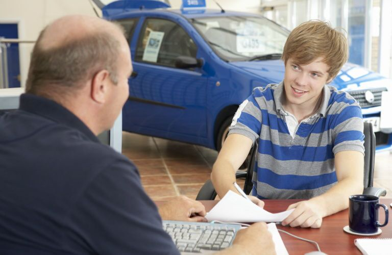 Young man signing papers for a used car loan